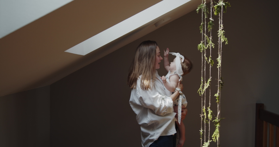 Mother and daughter spend time at home together. Young mom holds her little baby girl close to her standing under the window playing with hanging decoration. Parent care and child safety.   Shutterstock HD Video #1074683366