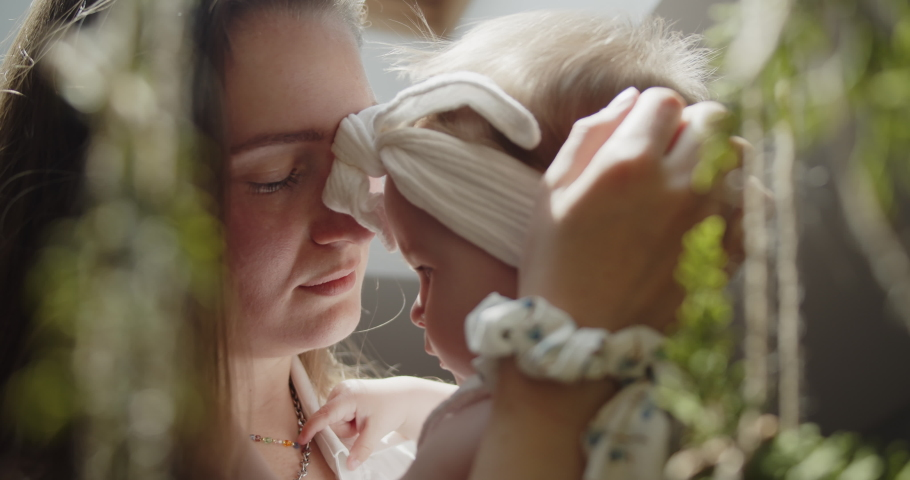 Mother and daughter spend time at home together. Young mom holds her little baby girl close to her standing under the window. Parent care and child safety. Close-up slow motion portrait.   Shutterstock HD Video #1074683372