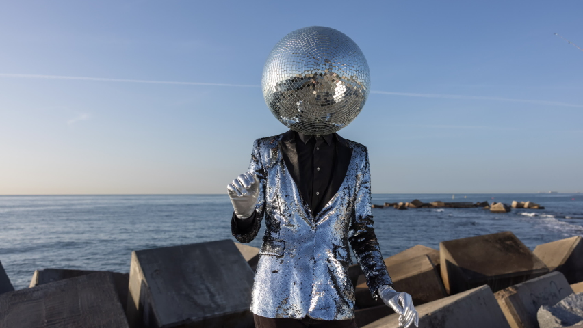 Mr discoball with a mirror ball as a head dancing by the sea on the coast in sunlight   Shutterstock HD Video #1074683579