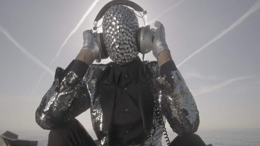 Mr disco man with a shiny mirror effect face wearing listening to music on headphones   Shutterstock HD Video #1074683582