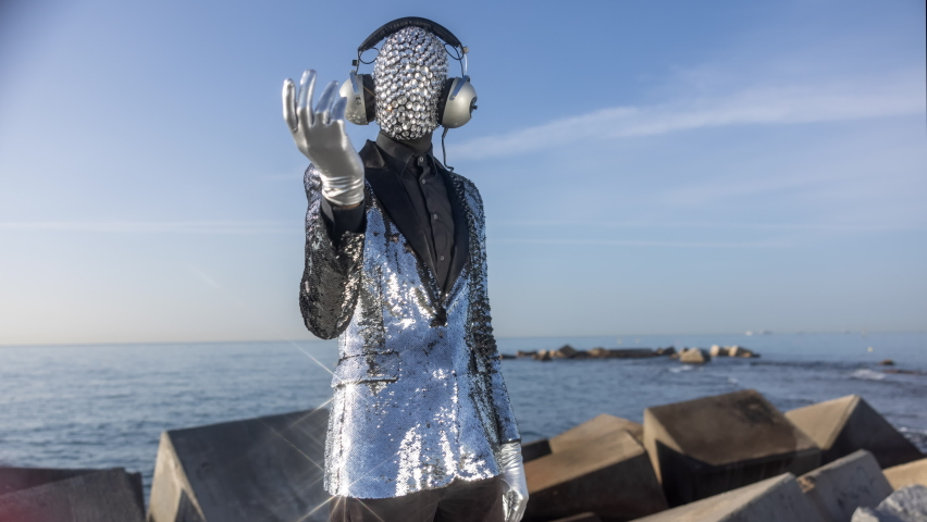 Mr disco man with a shiny mirror effect face wearing headphones next to the sea   Shutterstock HD Video #1074683585