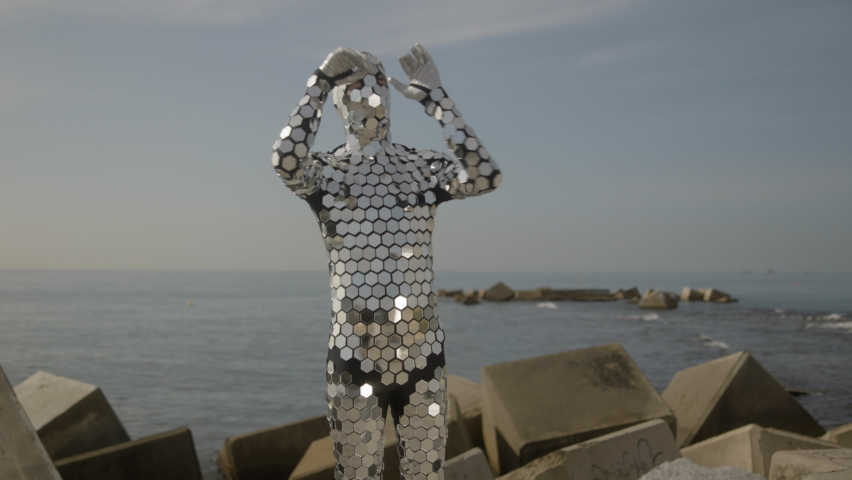 A man in a full body disco suit dancing next the sea in the morning sunlight   Shutterstock HD Video #1074683591