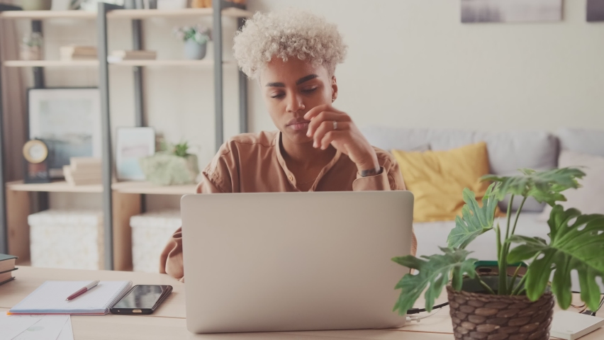 Thoughtful concerned African American female working on laptop computer looking away thinking solving problem at home office, serious woman search for inspiration make decision feel lack of ideas Royalty-Free Stock Footage #1074683633