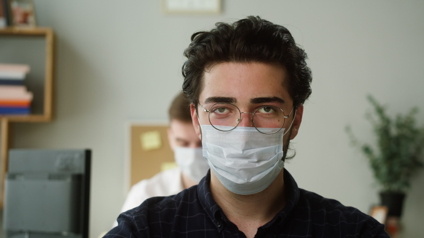 Portrait of serious Spain worker man wearing circle glasses and medical mask. Close-up of strict male employee sitting at workplace in office. Businessman in formal casual uniform looking in camera.    Shutterstock HD Video #1074683720