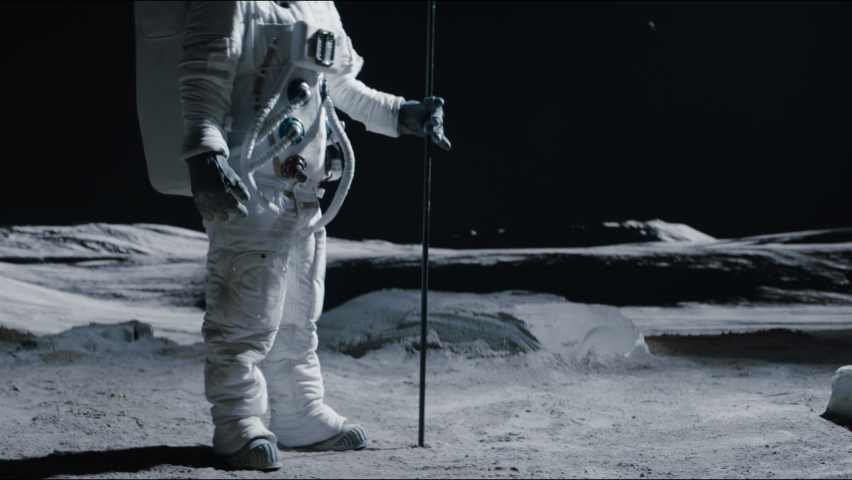 Portrait of Asian lunar astronaut standing with a flag pole on the Moon surface. Easy to track and add your flag. Shot with 2x anamorphic lens   Shutterstock HD Video #1074684290