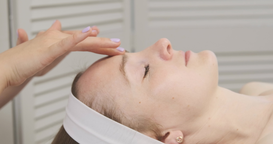 Hands of the masseur massage the face of a beautiful woman. Young woman in a spa salon. Facebuilding procedure. Modeling facial massage   Shutterstock HD Video #1074685370