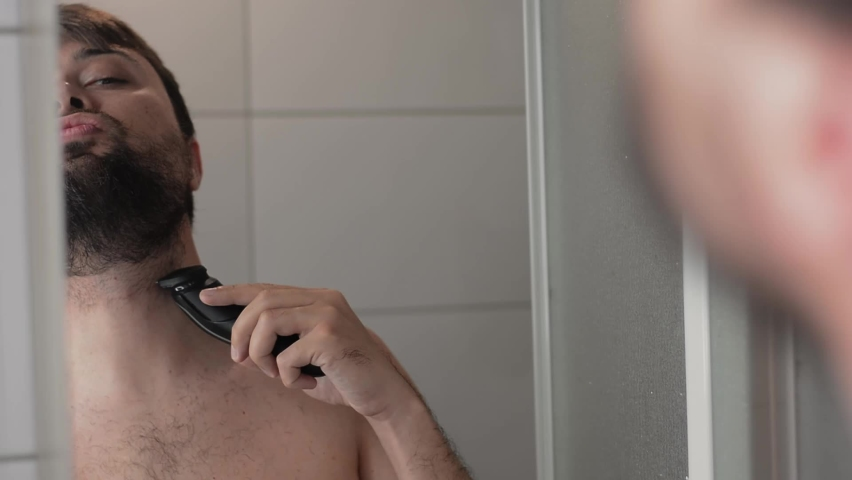 Close-up of the man shaves his beard neck and looks into the mirror reflection   Shutterstock HD Video #1074687434