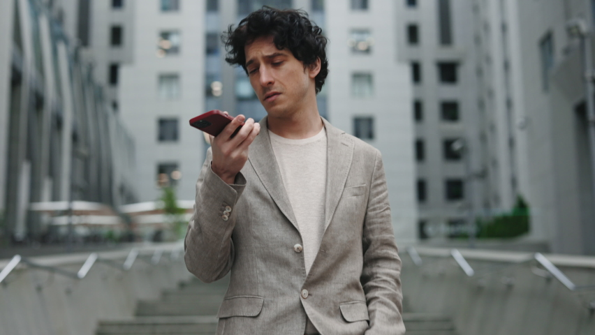 Waist up portrait view of attractive young businessman using smartphone while having conversation with his colleague. Male recording messages while walking near modern office building   Shutterstock HD Video #1074691682
