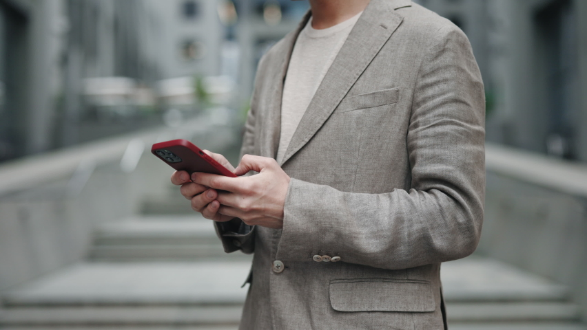 Cropped view of the caucasian confident young businessman using his smartphone app outside near the modern office building. People and technologies concept   Shutterstock HD Video #1074691685