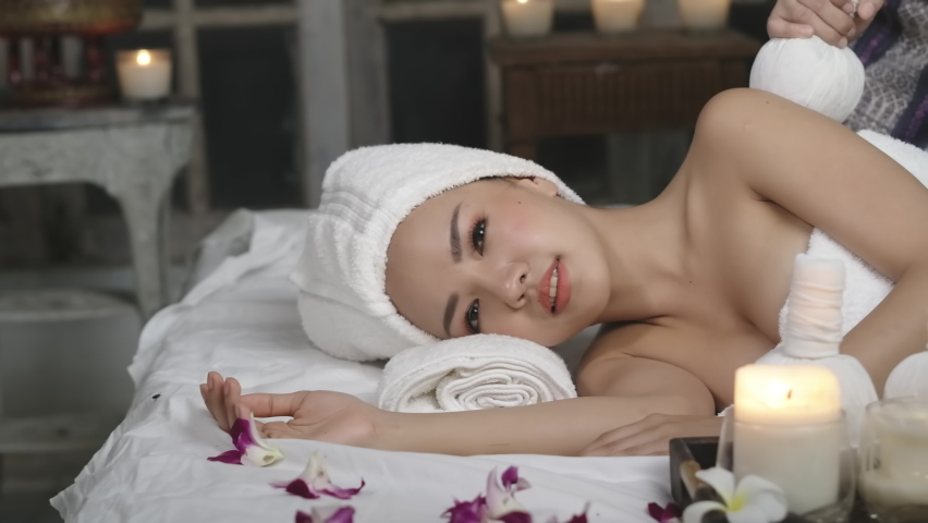 Beautiful woman line down on floor getting spa and massange serivce, happy woman with healthy lifestyle in romanstic spa room   Shutterstock HD Video #1074700493
