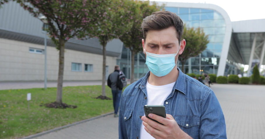 Close up man wearing protective face mask use phone. COVID-19 coronavirus infection near airport pandemic disease virus male tourist epidemic air health illness slow motion   Shutterstock HD Video #1074709913