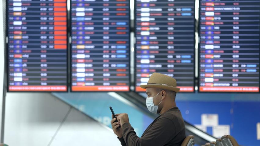 Traveler man wearing mask protect flu coronavirus. Tourist in airport terminal using smartphone sitting and waiting his flight. During the pandemic must be social distancing self quarantine.   Shutterstock HD Video #1074709937