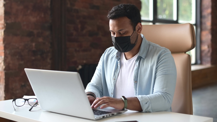 Indian man with a protective medical mask on the face sitting in the office and typing on the laptop computer, . Precautionary measures for office employees during pandemic, epidemic   Shutterstock HD Video #1074713087