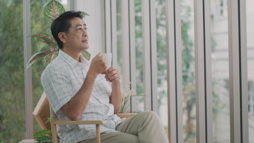 Morning elderly Asian man drinking coffee looking out of the window shows a look of unease   Shutterstock HD Video #1074715247