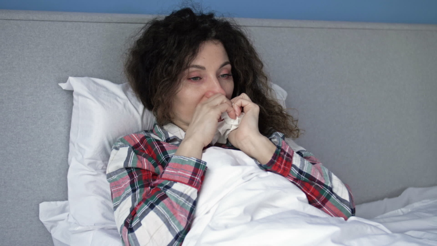 Portrait of a sick middle aged woman with symptoms of flu, cold or coronavirus. Condition after vaccination.   Shutterstock HD Video #1074715274