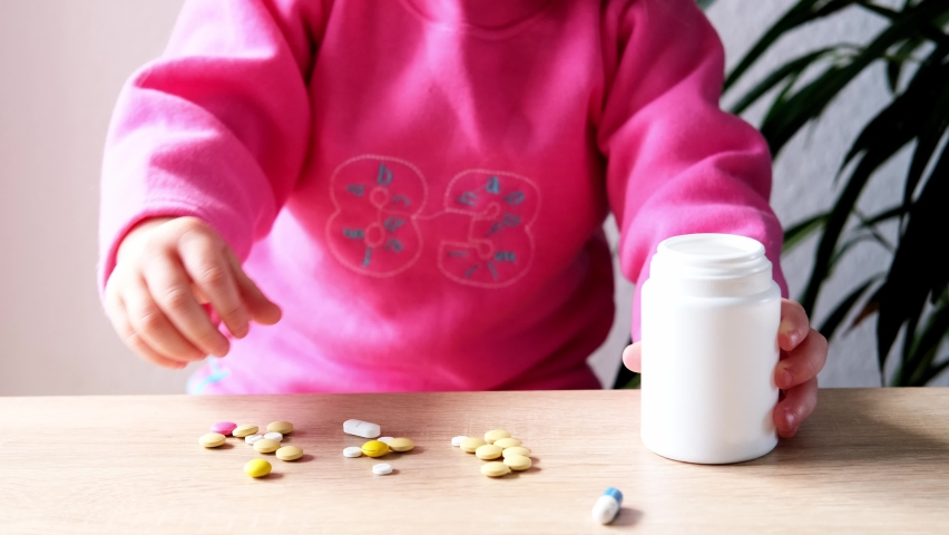 Female hand of a small child, baby, girl playing with medical pills, hazardous to health, drug poisoning concept, poor babysitting   Shutterstock HD Video #1074715832