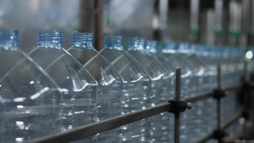 Empty plastic bottles with a volume of 5 liters move along the conveyor in the workshop of the mineral water bottling plant. Production of drinking water at a food processing plant | Shutterstock HD Video #1074717713