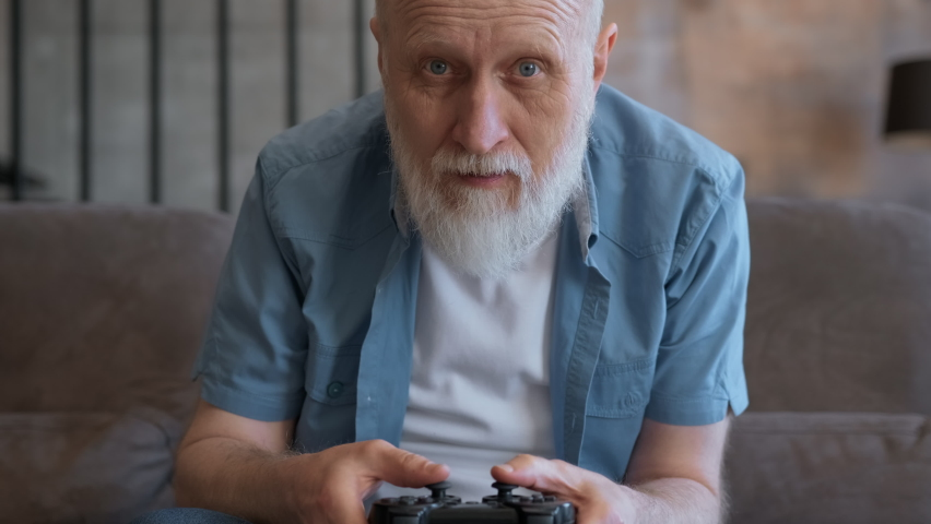 Old gray-haired pensioner, sitting on couch, emotionally plays on console, loses game, emotions of defeat. Portrait of an elderly man playing video game with wireless controller with joy of victory. | Shutterstock HD Video #1074717863
