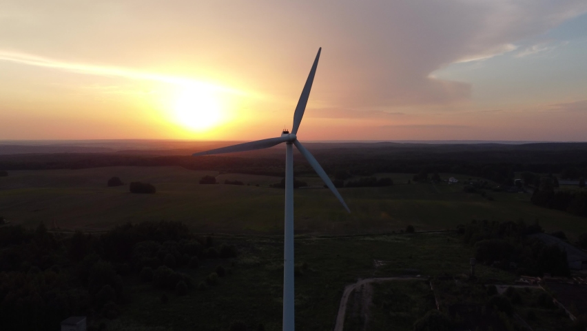 Drone Flies Over Large Wind Turbine with Blades. Aerial View of a Silhouette of a Windmill Against the Background of an Orange Sunset. Wind Power Turbines, Clean Renewable Energy, Alternative energy.  | Shutterstock HD Video #1074717866