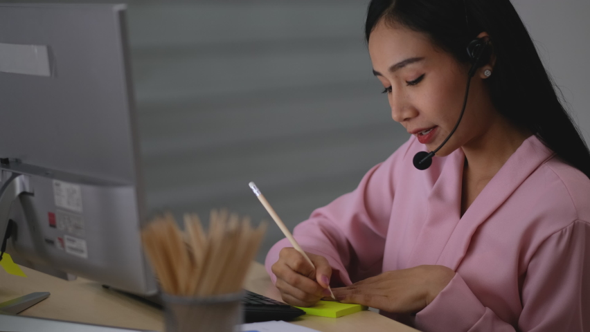 Close up business woman work as call center or operator use pencil write note on paper and stick to warning on computer monitor during work at night in office. | Shutterstock HD Video #1074718061