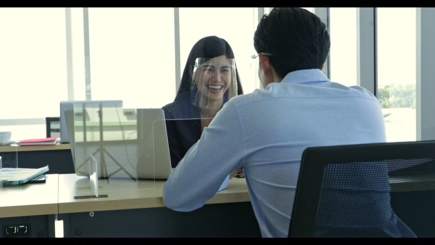 Slow motion of business conversation between businessman and women wearing protective face shield through the partition in office prevents covid - 19. Concept of new normal and social distancing. | Shutterstock HD Video #1074718082