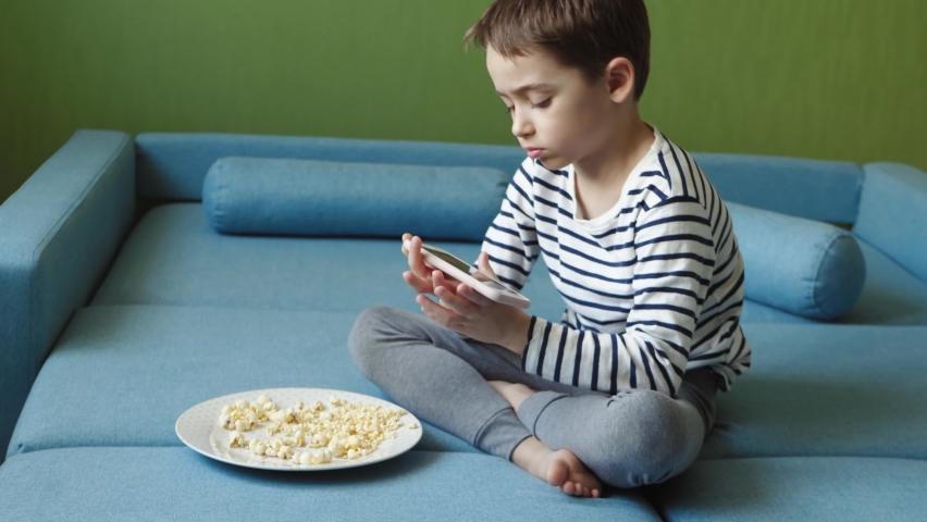 A beautiful boy spends time on the Internet using a smartphone. The child eats popcorn and plays games in the app. children and the internet. children's lifestyle | Shutterstock HD Video #1074718316