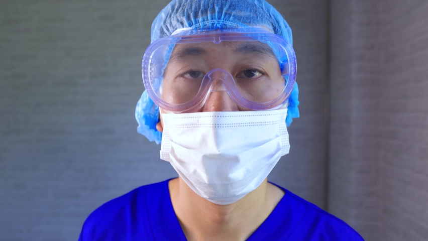 Asian male medical worker in ppe uniform and face mask working at hospital diagnosing and examining Covid-19 patients. Young nurse taking a nasal swab specimen to test for Corona virus infection.   Shutterstock HD Video #1074718625