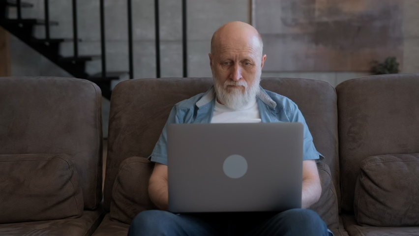 Old person works at laptop on Internet, looks through news, searches in Internet browser, remote work at distance at home. Elderly businessman grandfather works on computer sitting on couch at home. | Shutterstock HD Video #1074719003