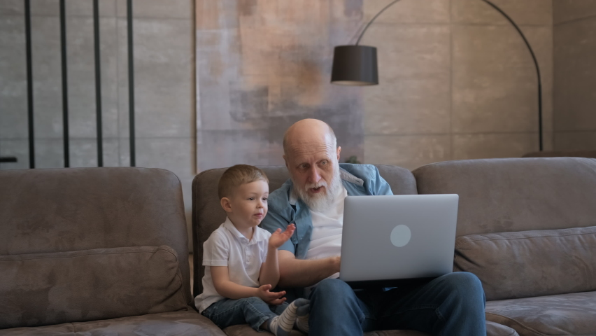 Happy old grandfather and cute little grandson laughing, happy raising their hands up looking at laptop, happy victory, sitting on couch at home. Grandfather and child are happy to win or win game. | Shutterstock HD Video #1074719006