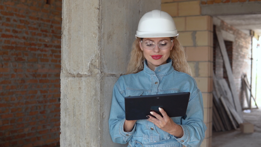 A female architect or mason stands in a newly built house with untreated walls and works on a tablet. Modern technologies in the oldest professions | Shutterstock HD Video #1074719444
