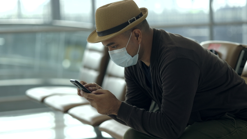 Young traveler man wearing mask protect flu coronavirus. Tourist in airport terminal using smartphone sitting and waiting his flight. During the pandemic must be social distancing self quarantine.   Shutterstock HD Video #1074720029