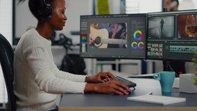 Black woman video editor editing new project film montage sitting in modern creative agency office. Content creator in digital multimedia company processing movie with post production software
