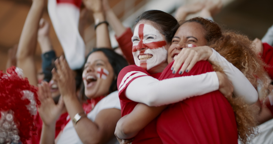 Female soccer fans of England watching and starts celebrating after their team's victory. English female spectators enjoying after a win at stadium.