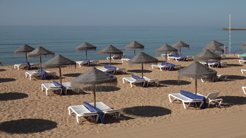 Empty sunbeds on beach symbolizing crisis in tourism sector in Southern Europe. Portugal eases lockdown restrictions and prepares for Summer holiday.  Royalty-Free Stock Footage #1074830129