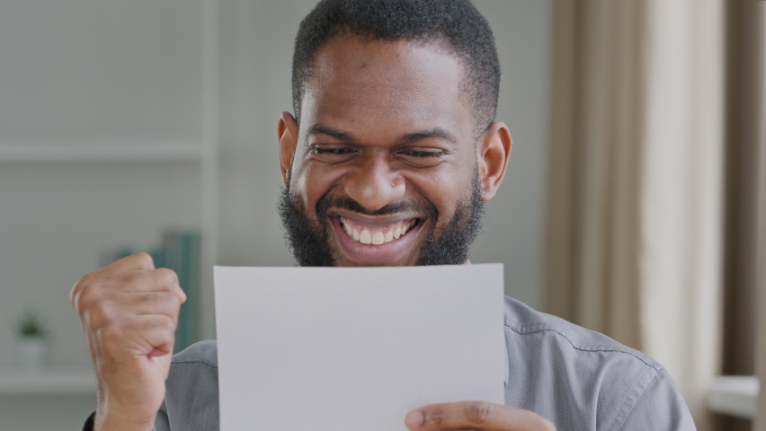 Excited black male executive receiving mail with salary growth payment, business loan approval. Happy overjoyed businessman opening envelope reading great news in paper letter sitting at workplace Royalty-Free Stock Footage #1074916928