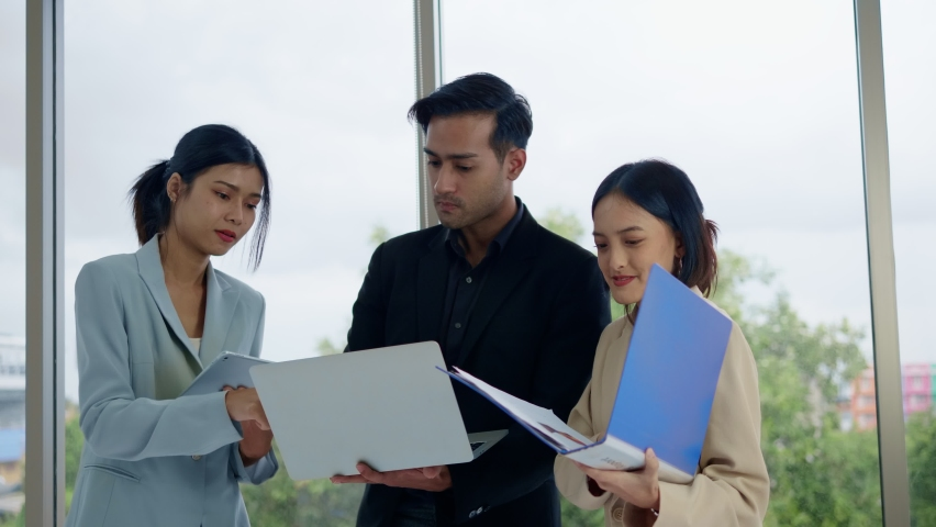 A new generation of asia business men and women in casual wear meet and brainstorm on new document projects. working together in planning strategies for success with teamwork.