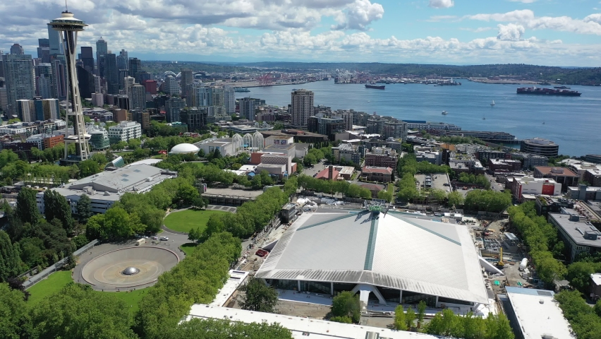 Cinematic 4K aerial drone footage of the Climate Pledge Arena near the International Fountain, Seattle Space Needle at Seattle Center, with Elliott Bay, Port of Seattle in the background