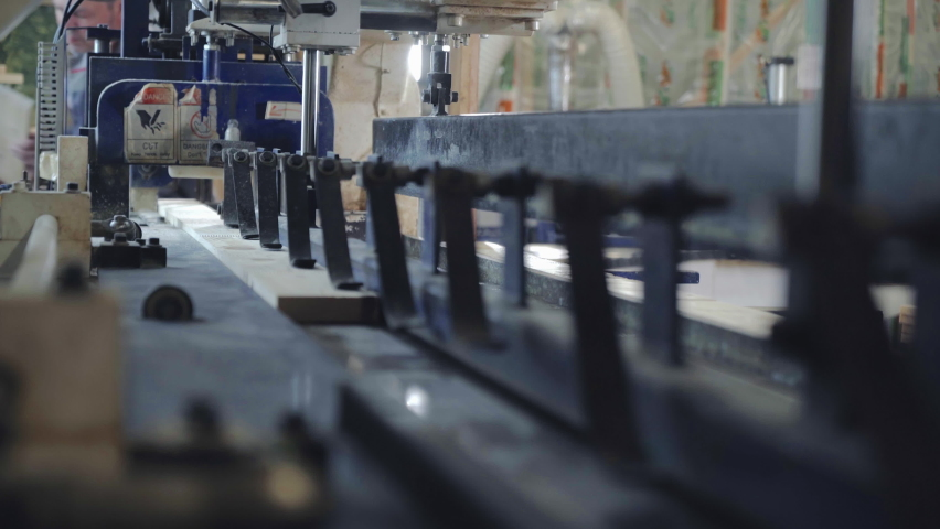 Newest equipment is used at the Modern Sawmill Facility. Putting the pieces of the wooden board inside of the equipment at the sawmill. Gluing Equipment is connecting the boards at the sawmill.   Shutterstock HD Video #1075042334