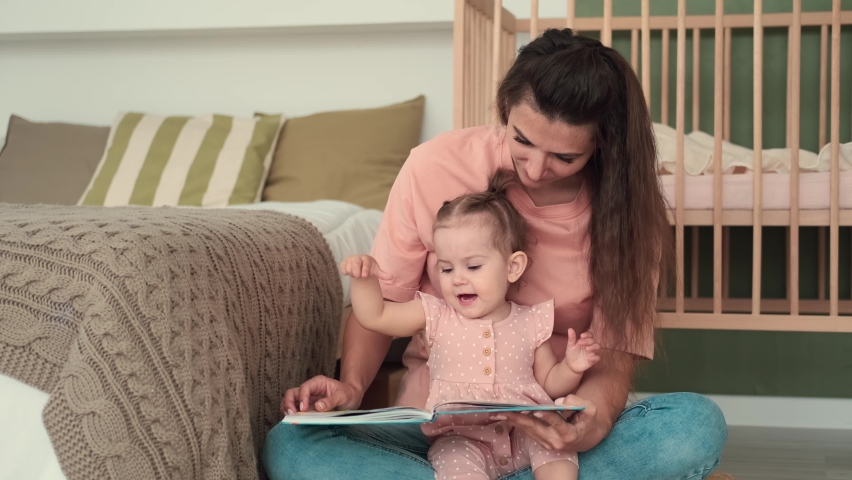 Childcare at Home, Child Protection, New Life, Leisure with Baby. Mom reads a book to the kid while sitting near the bed at home Royalty-Free Stock Footage #1075200728