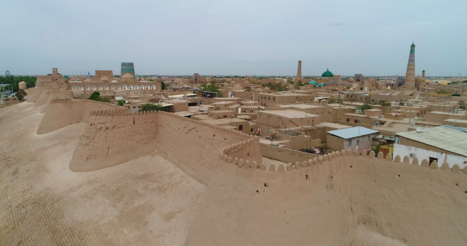 Aerial Forward Shot Of Religious Structures And Houses In Itchan Kala Surrounding Wall Against Clear Sky - Khiva, Uzbekistan   Shutterstock HD Video #1075244294