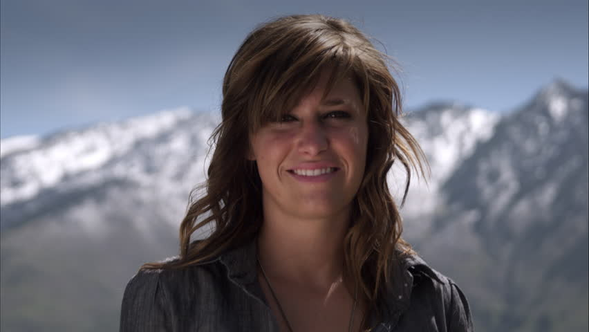 Slow motion shot of a woman smiling while on horseback with snowcapped mountains in the distance. Filmed with a high speed camera. #10752500