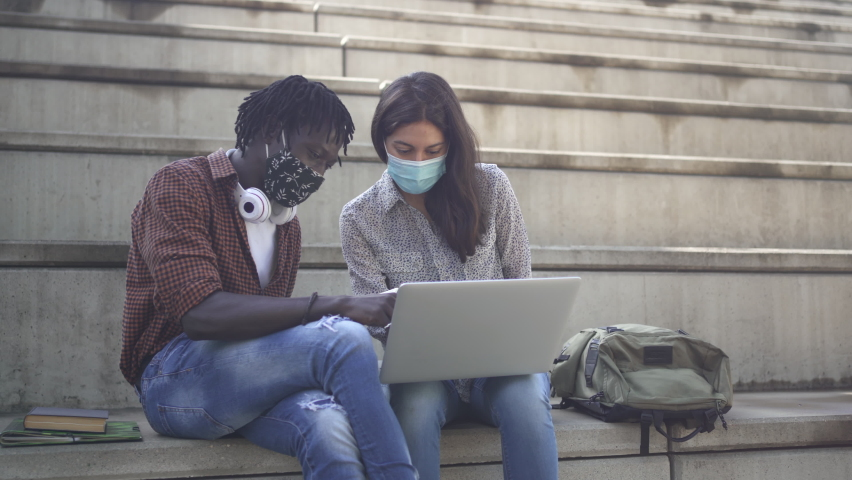 Diverse multi ethnic friends with face mask working and studying together outdoors in the staircase of an University Campus. African and Latin students have discussion and use laptop  Royalty-Free Stock Footage #1075252538