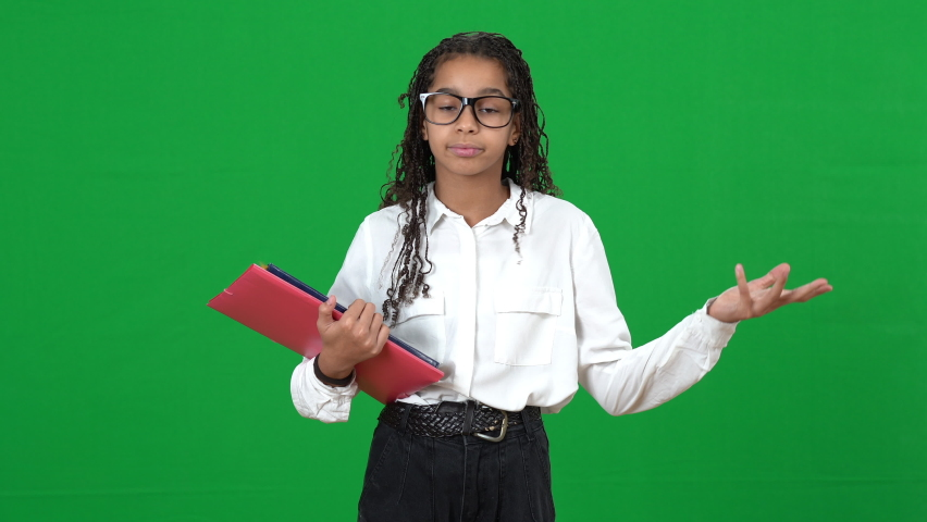 Portrait of nerd African American teen girl in eyeglasses looking through notes in workbook sighing looking at camera with dissatisfied facial expression on green screen. Bored genius at chromakey Royalty-Free Stock Footage #1075274129