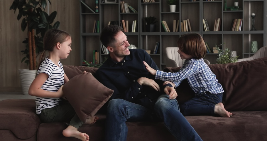 Cheery dad play with little son and daughter at home. Happy carefree family tickling each other laughing having fun together on sofa at modern cozy living room, playtime with kids on weekend concept
