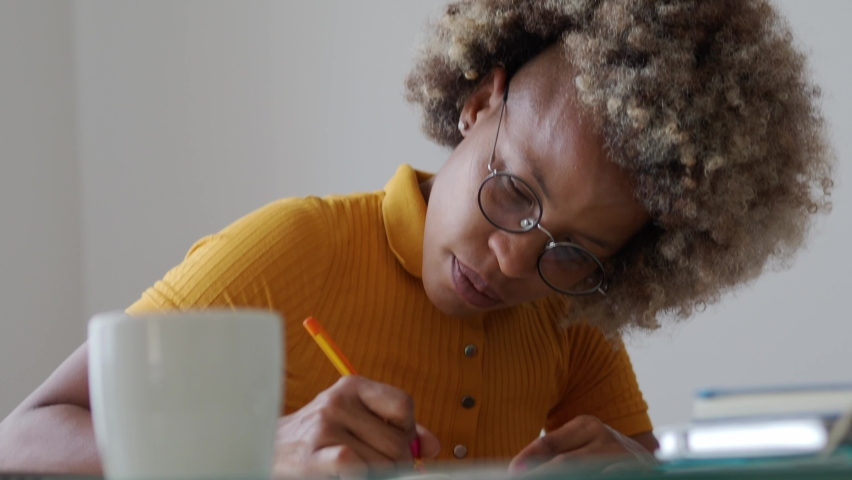 African American woman writing in a notebook at home while working. Work at home, writer, content creator Royalty-Free Stock Footage #1075397126