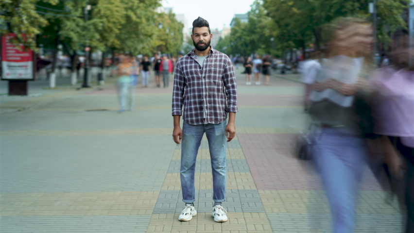 Zoom-in time lapse portrait of attractive Middle Eastern man standing alone among people passing by and looking at camera with serious face. Youth and society concept.