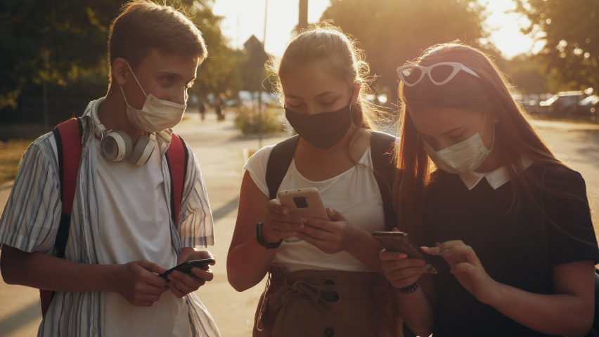 A group of teenagers with protective masks on their faces are talking in the middle of a city street with smartphones in their hands Royalty-Free Stock Footage #1075558634