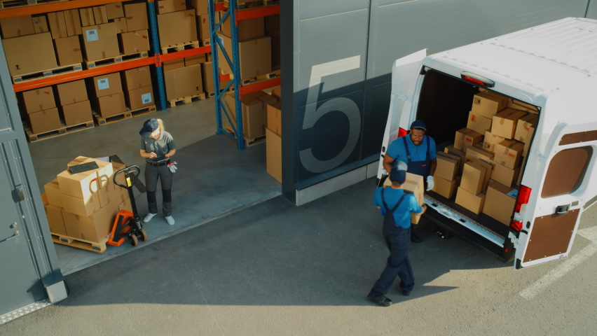 Outside of Logistics Retailer Warehouse With Manager Using Tablet Computer, Workers Start Loading Delivery Truck with Cardboard Boxes. Online Orders, Purchases, E-Commerce Goods. High Angle Shot