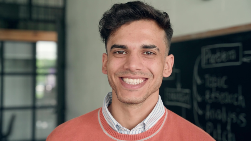 Young happy smiling cheerful Indian latin guy Hispanic high school college university student standing in classroom campus laughing looking at camera. Headshot close up portrait. Royalty-Free Stock Footage #1075721753