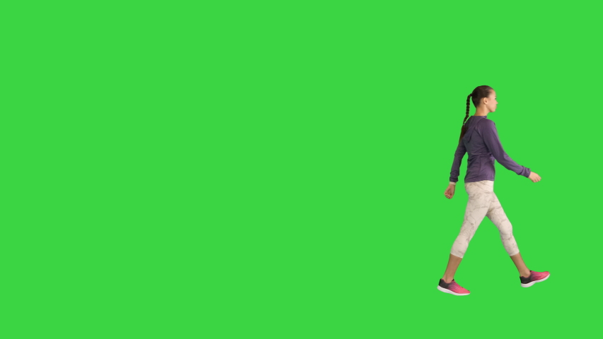 Young woman using her smart watch while walking on a Green Screen, Chroma Key.